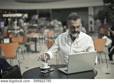 man works with a computer in a cafe