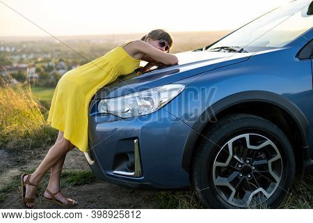 Happy Young Woman Driver In Yellow Dress Enjoying Warm Summer Evening Leaning On Her Car.