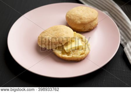 Homemade Flaky Buttermilk Biscuit On A Pink Plate On A Black Surface, Low Angle View. Close-up.