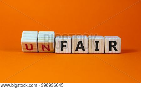 Fair Or Unfair Symbol. Turned A Cube And Changes Words 'unfair' To 'fair'. Beautiful Orange Backgrou