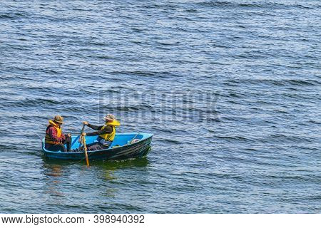 Stewart Island New Zealand - November 2020; Two Men In Small Blue Dinghy One Rowing While Other Fish