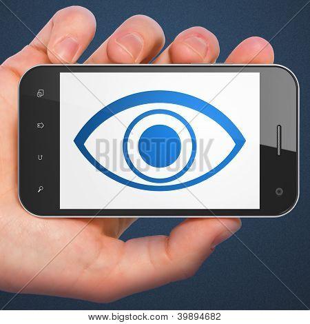 Hand holding smartphone with eye on display. Generic mobile smar