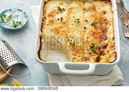 Cheesy Scalloped Potatoes With Thyme And Parmesan With A Piece Taken Out