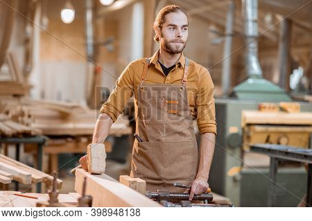 Portrait Of A Handsome Carpenter, Standing Near The Workbench At The Old Craft Joinery