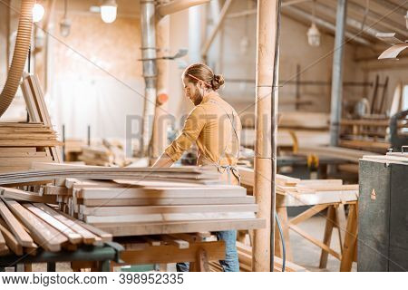 Carpenter Carrying Pine Planks In A Carpentry Workshop Warehouse. Preparing Raw Materials For The Fu