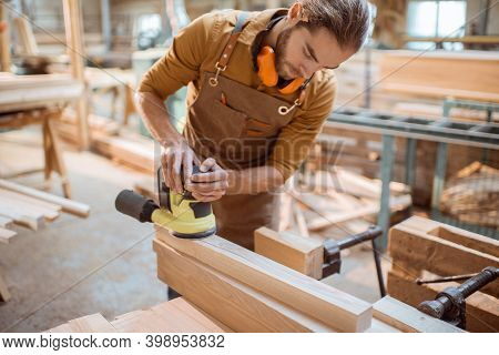 Carpenter Grinding Wooden Bar With A Cordless Grinding Machine In The Workshop