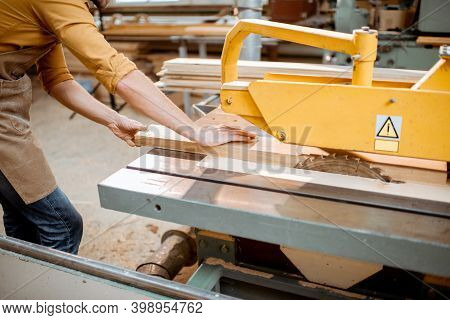 Carpentry Worker Sawing Wooden Planks With Circular Saw In The Joinery Warehouse. Close-up With No F