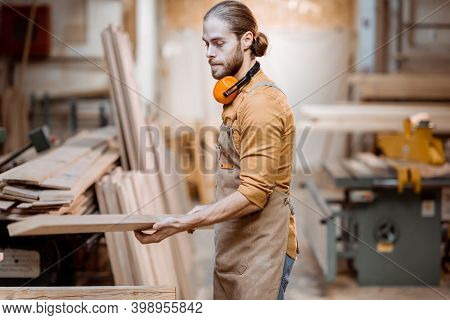 Handsome Carpenter Choosing Planks For His Woodwork At The Joiners Warehouse