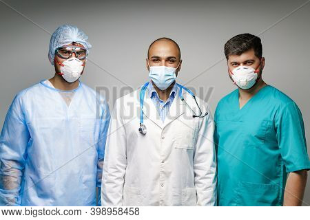 Male Doctors In Medical Uniform Wearing Masks Standing Against Grey Background