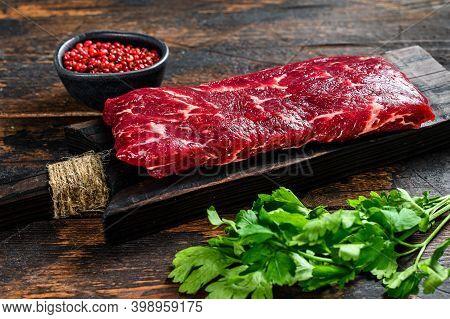 Raw Skirt Or Machete Beef Meat Steak On A Cutting Board. Dark Wooden Background. Top View