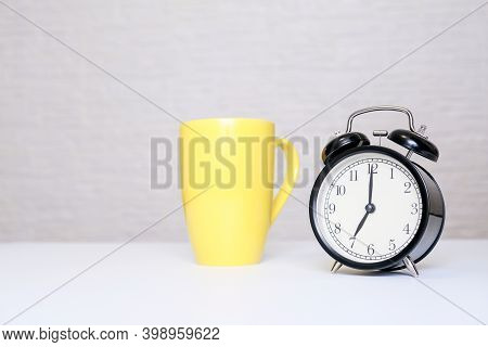 A Big Yellow Cup Of Coffee And Alarm Clock Showing 7 Am On A Table, Ready For Work Concept, Copy Spa