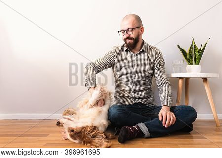 Man Pets His Dog Sitting On The Floor At Home. Indoor Life, Quarantine, Finding Simple Joy At Lockdo
