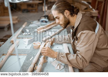 Manual Worker Finishing Wooden Products, Spackling And Grinding Baluster At The Carpentry Manufactur