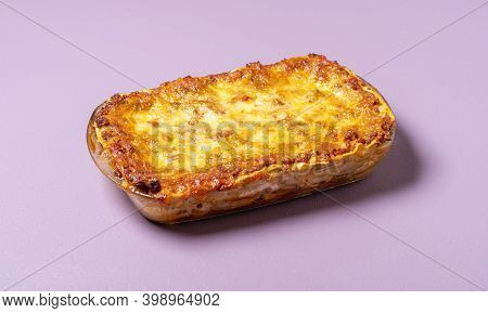 Meat Lasagna In Tray, Freshly-baked, On Purple Background. Homemade Traditional Italian Lasagna With