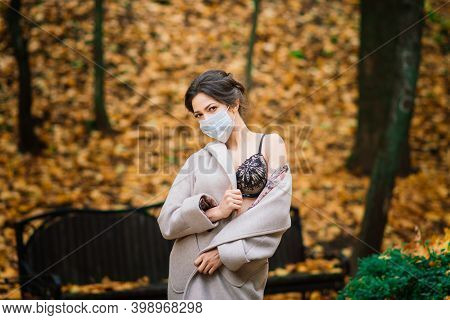 Fashion Portrait Of Sexy Woman In Mask And Lingerie In Autumn Park. Pandemic, Virus, Coronavirus