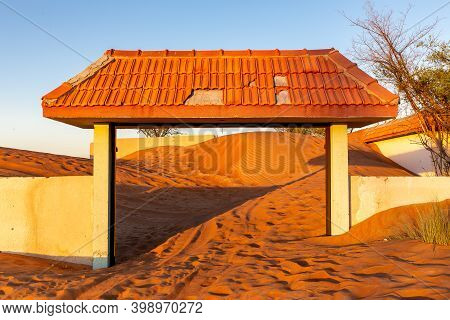 Wall And Tiled Gate Buried In Sand Dunes In The Desert In Al Madam Ghost Village, United Arab Emirat