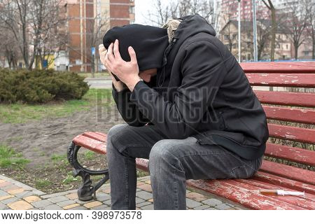 An Addict On The Street In Crisis After Taking Drugs. Addiction Concept. Dependence, Overdose