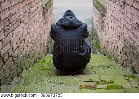 Addiction Concept. A Drug Addict In A Hood Sits In An Abandoned House After Taking Drugs. Fighting A