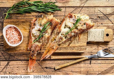 Grilled Red Seabass On A Cutting Board. Wooden Background. Top View