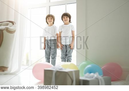 Lovely Twins. Two Cute Latin Twin Boys, Little Children In Casual Wear Looking Happy, Greeting Their