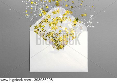 Sparkling Golden Confetti Pouring Out Of White Envelope On Gray Background. View From Above. Flat La