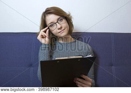 Portrait Of A Confident Young Psychotherapist Taking Notes And Looking At Camera. Female Doctor, Psy