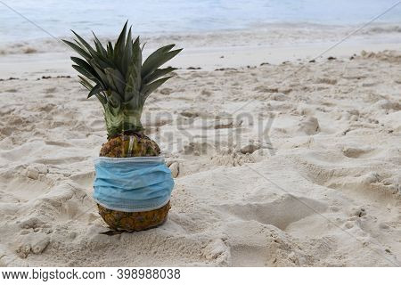 Pina Colada In Pineapple In Protective Face Mask On The Sand On The Coast Caribbean Sea. Vacation An