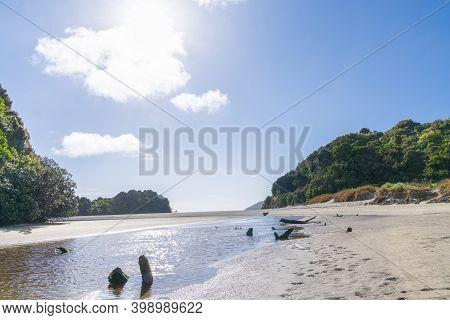 Shallow Stream Across Low Tide Beach Looking Into Sun In Idyllic Summer Beach Scene At Mill Creek, S