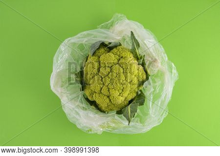 A Green Cauliflower In A Bag On A Green Surface