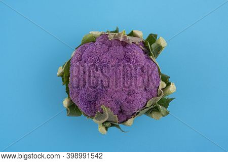 A Violet Cauliflower In A Bag On A Blue Surface