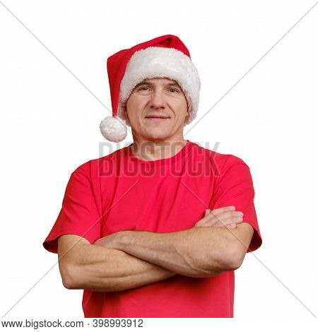 Portrait Handsome Man Wearing Santa Hat And Red Informal T-shirt With Folded Arms Isolated On White