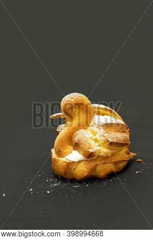 Flaky Cream Puff Dessert In The Shape Of A Swan On A Black Background.