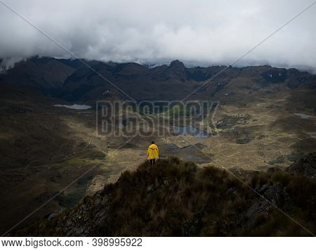 Person In Yellow Jacket Infront Of Andes Hills Tundra Grassland Lakes Landscape In El Cajas National