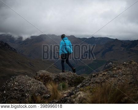 Hiker In Blue Jacket Infront Of Andes Hills Tundra Grassland Lakes Landscape In El Cajas National Pa