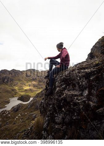 Hiker Resting In El Cajas National Park, Hills Tundra Grassland Lakes Landscape In Cuenca Ecuador An