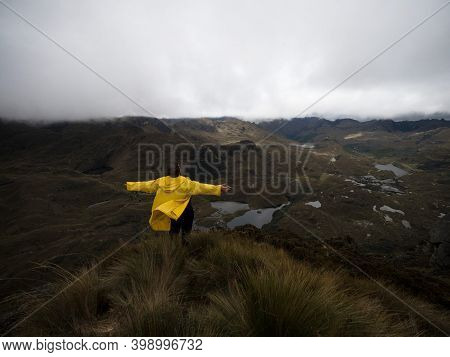 Person In Yellow Jacket Infront Of Hills Tundra Grassland Lakes Landscape In El Cajas National Park