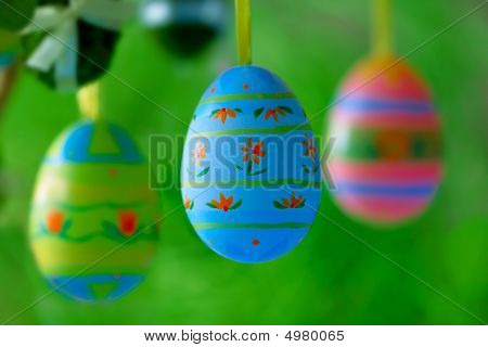 Painted Easter Eggs Hanging Over Natural Green Background