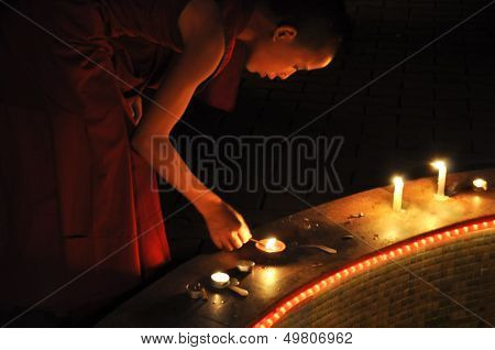 Young Buddhist Monk Lighting Candles