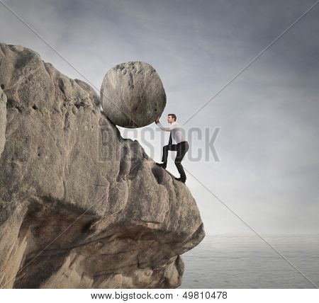 fatigued businessman supports large boulder