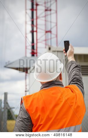Employee with the cell phone near to gsm tower before the rain