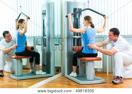 Patient at the physiotherapy or physical therapy doing exercises with her therapist