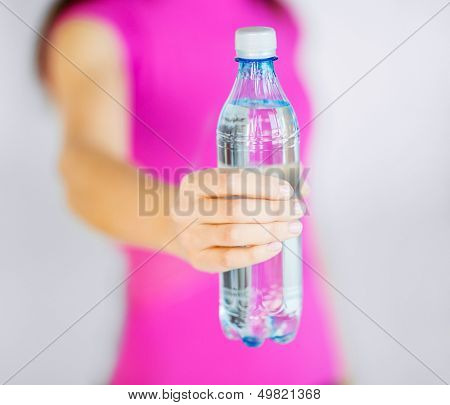 sport and diet concept - sporty woman with bottle of water