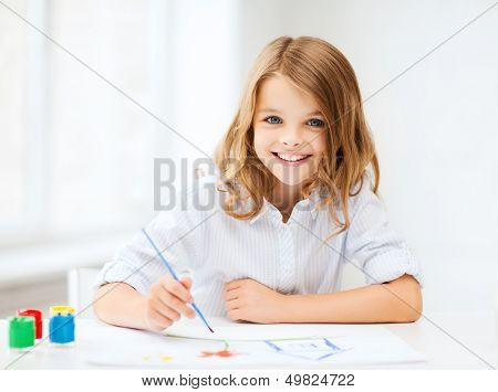 education, school, art and painitng concept - little student girl painting at school