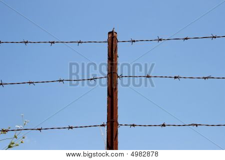 Three Strands Of Barbed Wire On Rusty Post Over Sky