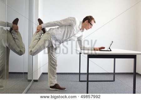 leg exercise durrng office work - standing man reading at tablet in his office