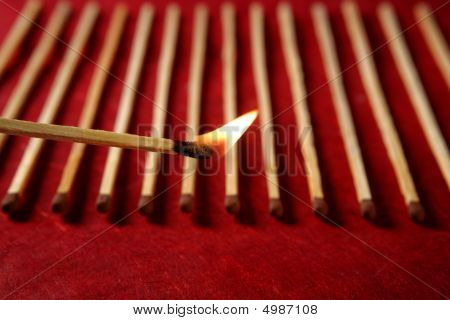Light wooden matches arrangement in a row over red background poster