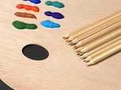 A colourful image of pencils and paints laying on an Artists palette poster