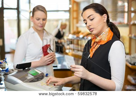 Client at shop paying at cash register with saleswoman poster