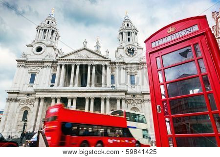 St Paul's Cathedral in London, the UK. Red bus and telephone booth, cloudy sky. Symbols of London