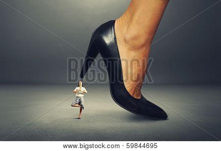 calm businesswoman under big heel. isolated on white background